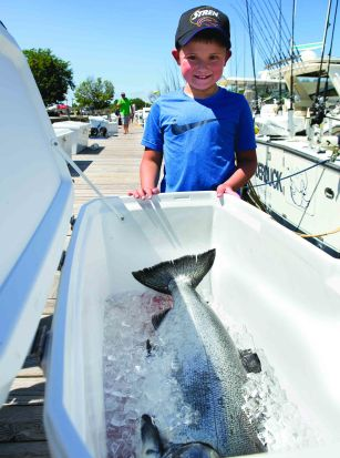 Andrews Mathews, 7, poses with his 26.8 pound king salmon, the heaviest catch of the day, during the 2018 Tri-Cities Kiwanis Salmon Tournament on Lake Michigan in Grand Haven, Mich., on Thursday, July 26, 2018. (Casey Sykes for Kiwanis Magazine)